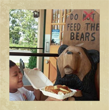 Kid offering food to a Black Bear Diner Wooden Bear