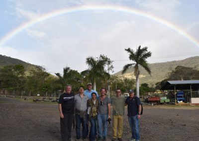 group photo with mountains and rainbow in background