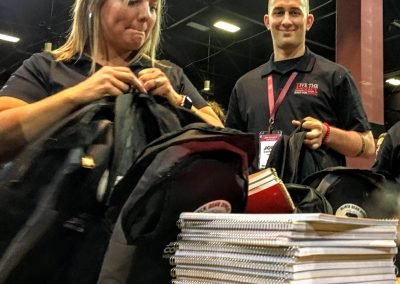 two team members putting notebooks in backpacks