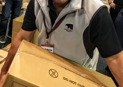 Team member smiling while carrying a full Java City box