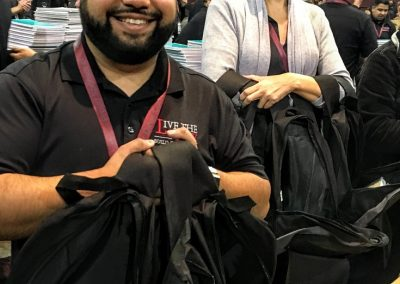 two team members smiling while filling the backpacks