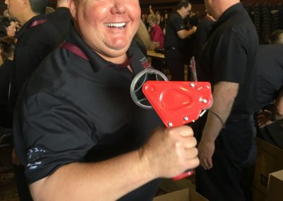 Team member smiling with a tape dispenser in his hand